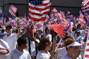Primary view of object titled '[Group of immigration protesters wave American flags]'.
