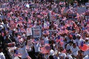 Primary view of object titled '[Protesters march with signs and American flags]'.