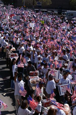 Primary view of object titled '[Immigration protesters march holding signs and American flags]'.