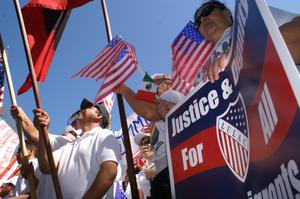 Primary view of object titled '[Immigration Protesters Hold Signs and American Flags]'.