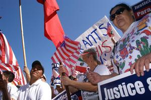 Primary view of object titled '[Immigration Protesters Hold American Flags and Signs]'.