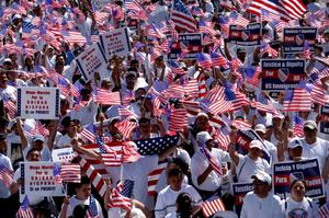 Primary view of object titled '[Large crowd of immigration protesters holding signs and waving American flags]'.