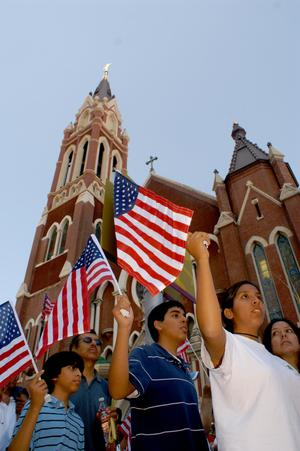 Primary view of object titled '[Protesters march and wave American flags as they pass Cathedral Santuario de Guadalupe in Dallas]'.