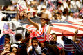 Photograph: [Female protester waves American flag above the crowd]