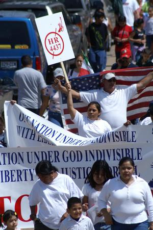 Primary view of object titled '[Protesters carry signs and a United States flag]'.