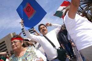 Primary view of object titled '[Protesters hold up signs and a Mexican flag]'.