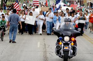 Primary view of object titled '[Group of protesters walking behind police officer on motorcycle]'.