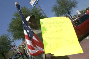 Primary view of object titled '[Man holding American flag and yellow handwritten sign]'.