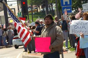 Primary view of object titled '[Male protester holding bright pink sign and American flag]'.