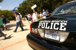 Primary view of object titled '[Protesters with signs and flags march past a Farmers Branch police car]'.