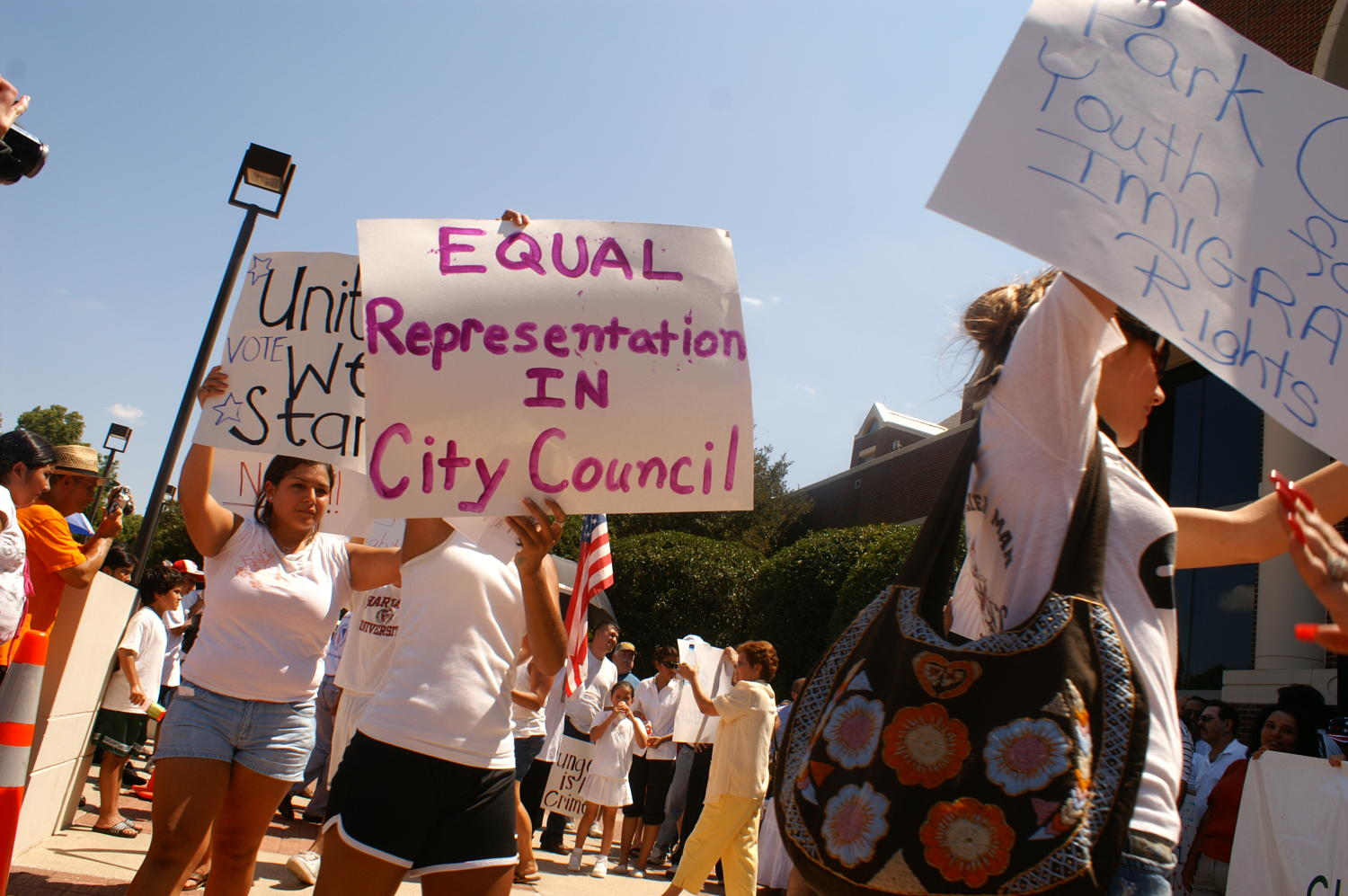 "[Protesters carry signs saying, ""United We Stand,"" and ""Equal Representation in City Council""]                                                                                                      [Sequence #]: 1 of 1"