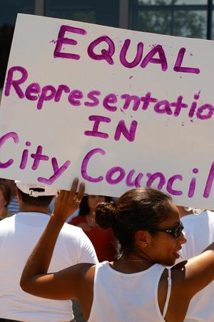 "Primary view of object titled '[Protester holds a sign, ""Equal  Representation in City Council""]'."