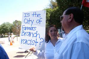 "Primary view of object titled '[Protester holding a sign, ""Is the city of Farmers Branch racist?""]'."