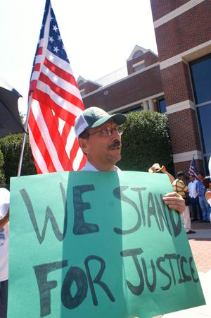 "Primary view of object titled '[Protester with an American flag and a sign, ""We Stand for Justice""]'."