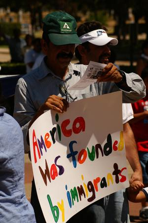 "Primary view of object titled '[Protester with sign, ""America was founded by immigrants""]'."