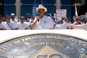 Primary view of object titled '[Speaker wearing a hat with a microphone and protesters behind him]'.