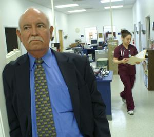 Primary view of object titled '[Eddy Herrera stands in a medical office while staff member walks by]'.
