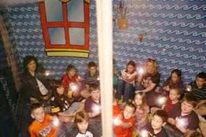 Primary view of object titled '[Teachers and students point flashlights at possible dangers in a home safety demonstration]'.