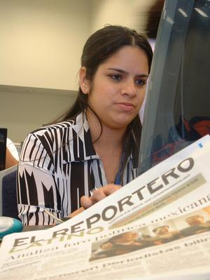 Primary view of object titled '[Aracelis Acevedo works on a computer as she writes for The Latino Reporter]'.